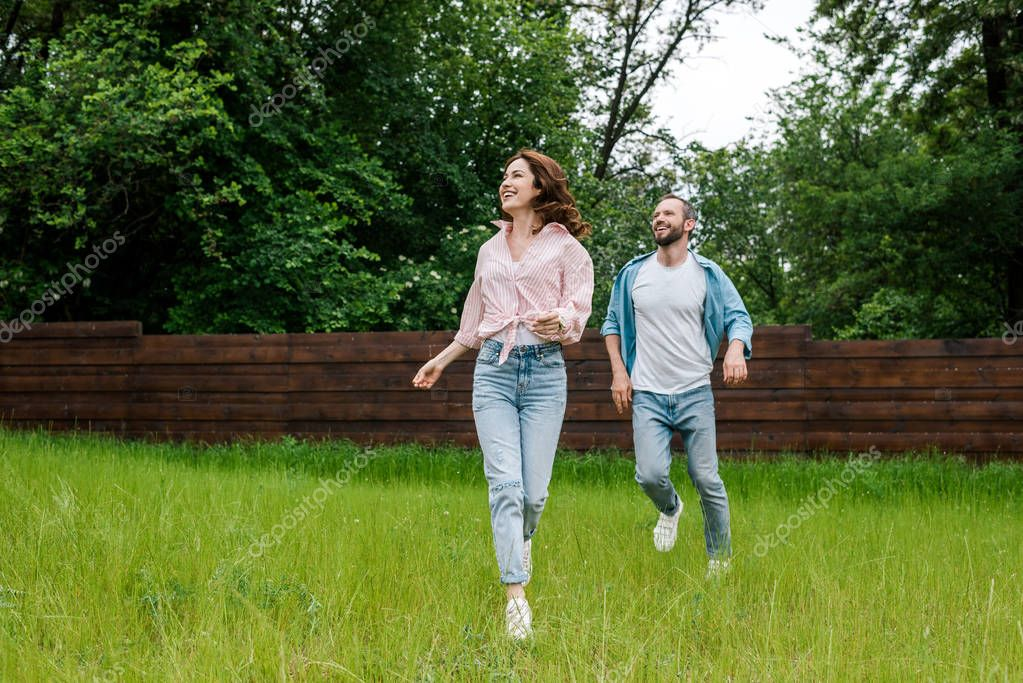happy man and woman running on green grass outside