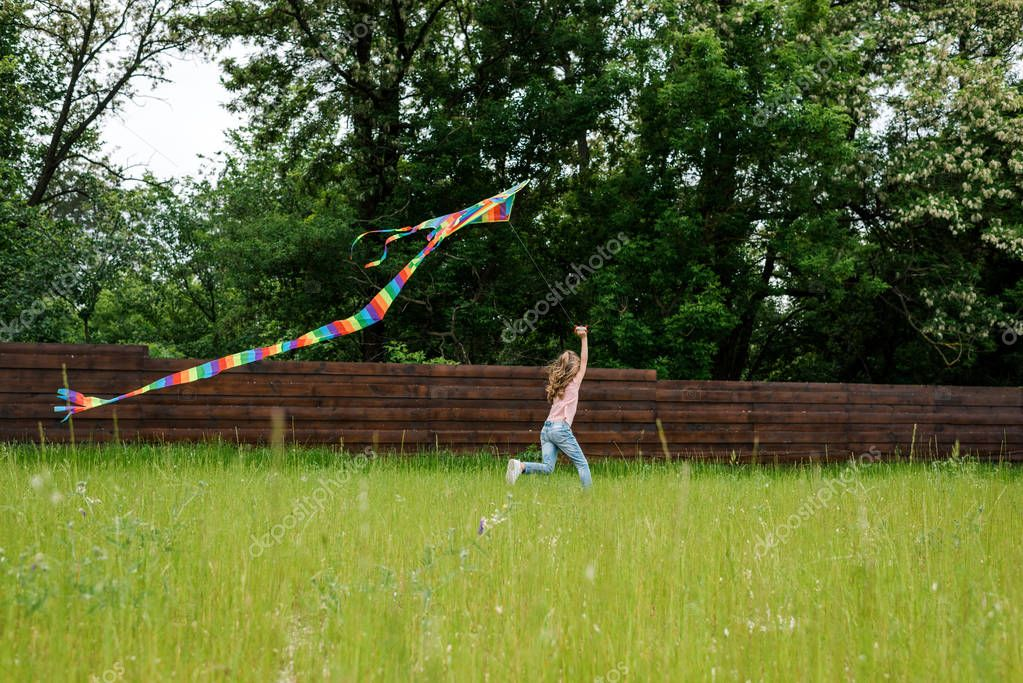 selective focus of child running with colorful kite on green grass outside