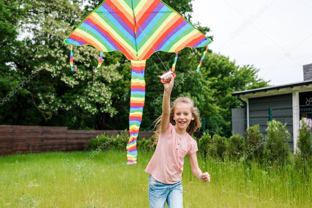 cheerful child running with colorful kite on green grass outside