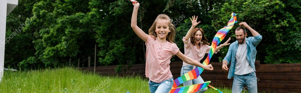 panoramic shot of happy kid running with colorful kite near cheerful parents
