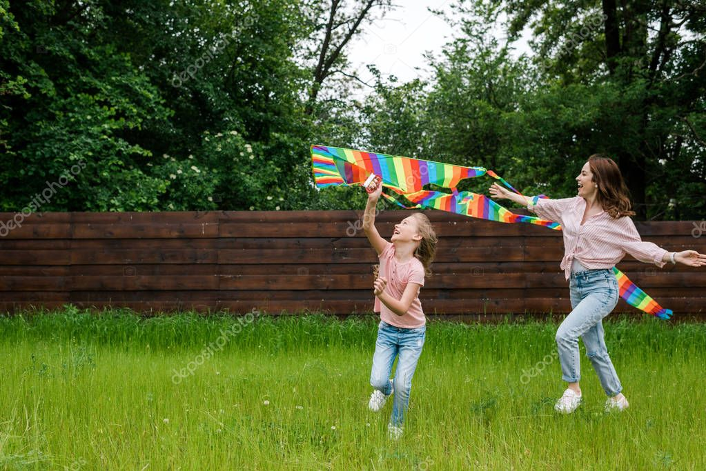 cheerful mother with outstretched hands near cute kid with colorful kite
