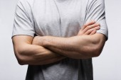 cropped view of man standing with crossed arms isolated on grey, human emotion and expression concept