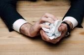 Teilansicht eines Geschäftsmannes, der am Tisch sitzt und Papier zerknüllt