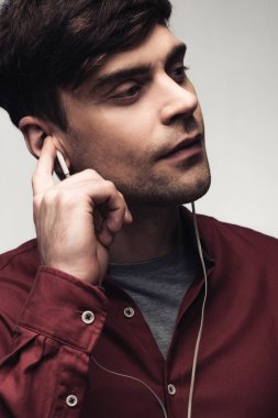 pensive man looking away while listening music in earphones isolated on grey