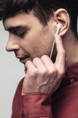pensive man listening music in earphones with closed eyes isolated on grey