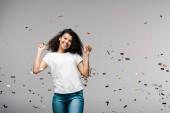 Veselé africké americké dívky usmívající se blízko lesklého konfetu, když stojí na šedé