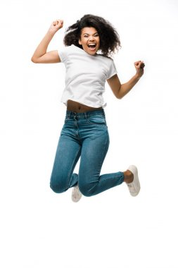 Happy african american woman gesturing while celebrating and jumping isolated on white stock vector