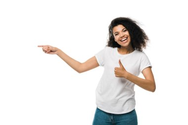 Cheerful african american girl showing thumb up and pointing with finger isolated on white stock vector