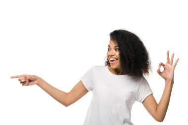 Cheerful african american woman pointing with finger while showing ok sign isolated on white stock vector