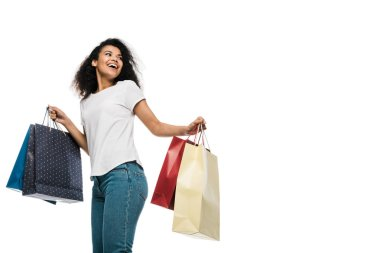 happy curly african american girl holding shopping bags isolated on white