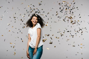 Happy young african american woman smiling near shiny confetti while standing on grey stock vector