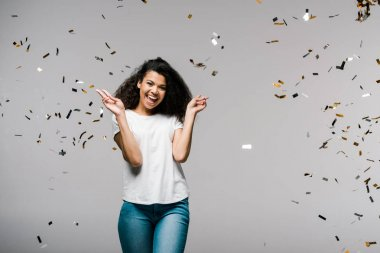 Young african american woman smiling near falling confetti while standing and showing peace sign on grey stock vector