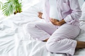 cropped view of african american pregnant woman touching belly on bed