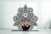 Photo calm asian woman with closed eyes sitting on yoga mat near mandala ornament