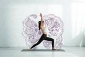 nyugodt ázsiai nő csinál jóga gyakorolja a jóga mat közel Mandala dísz
