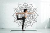 ázsiai nő gyakorlás jóga a jóga mat közelében Mandala ornament