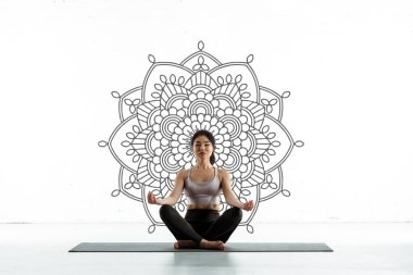 Calm thai woman practicing yoga on yoga mat near mandala ornament on white stock vector
