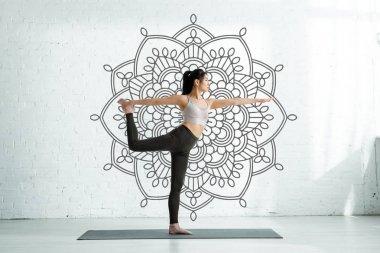 Asian woman practicing yoga on yoga mat near mandala ornament stock vector