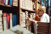 krásná a blondýnka v brýlích ukazováčku v knihovně v knihovnici