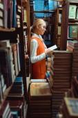 pohled na krásnou a blonďatou ženu v brýlích a pomerančových šatech čtení knihy v knihovně