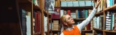 panoramatický záběr krásné a blond ženy v knize brýlí v knihovně
