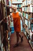 krásná a blondýnka v brýlích a oranžových šatech v knihovně