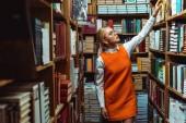 Blondýnka a krásná žena v oranžových šatech, držící knížku v knihovně