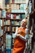 krásná a blondýnka s očima zamčřenými v brýlích s knihou v knihovně
