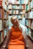 krásná a blondýnka s očima zavřenými v brýlích, které seděly na podlaze v knihovně