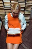 Nagy látószögű nézet gyönyörű nő ül a padlón, és olvasás könyv könyvtár