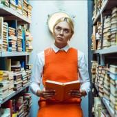 schöne und nachdenkliche Frau in orangefarbenem Kleid, Buch in der Hand und in Bibliothek aufblickend