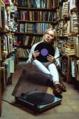 krásná a Blondýnka, která se dívá stranou a drží vinyl v knihovně
