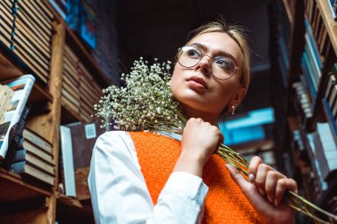 low angle view of woman in glasses holding white flowers and looking away in library