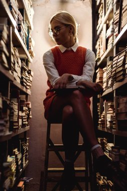 beautiful and blonde woman in orange dress sitting on ladder and holding book in library