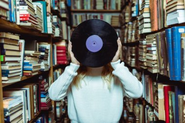 cropped view of young adult woman holding vinyl in library