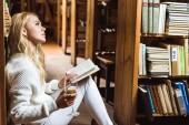 boční pohled na blonďatou a dresnou ženu drženou knihu a sklenku vína v knihovně