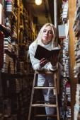 szőke és csinos nő a fehér pulóvert könyvet a könyvtárban