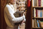 Photo cropped view of woman in white sweater holding books in library