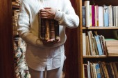 Photo partial view of woman in white sweater holding books in library