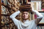 Blondýnka a přitažlivá žena s zavřenýma očima, které drží knihy v knihovně