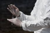 részleges kilátás a víz ellenőrhöz latex kesztyűben, vízminta-mintavételes kémcsőbe
