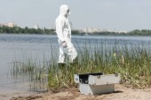 selective focus of water inspector in protective costume and inspection kit on foreground