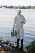 teljes hosszúságú kilátás a víz ellenőr védőöltözet gazdaság ellenőrzési Kit és lombik a folyón