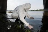 Fotografia ispettore dellacqua in costume protettivo e respiratore che prende il campione dacqua al fiume