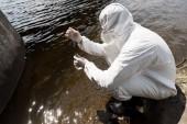 vízvizsgáló védőöltözet, latex kesztyű és vízpumpa a folyó vizével