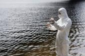 Fotografia ispettore dellacqua in costume protettivo, guanti di lattice e respiratore che prende il campione dacqua al fiume