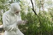 Fotografie ekolog v ochranném kostýmu, respirátoru a brýlí držící závod v lese