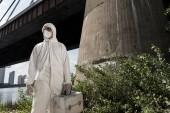 ecologista in costume protettivo con kit di ispezione in piedi vicino al ponte