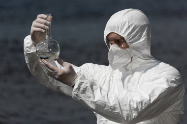 water inspector in protective costume, respirator and goggles holding flask with water sample