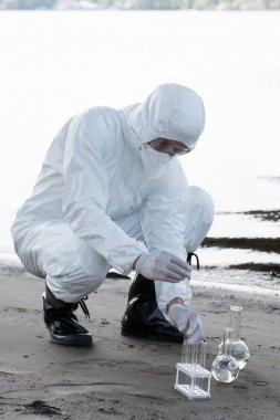 Water inspector in protective costume and respirator taking water samples at river stock vector